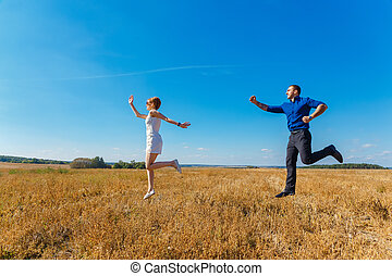 Young couple having fun on summer field