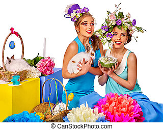 Woman in easter style holding eggs and flowers. - Women sit...