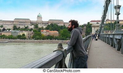 """one single man looking budapest castle view, chain bridge,..."