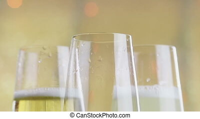 filling flutes of champagne with golden bubbles against gold...