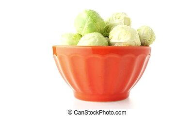 Fresh brussels sprouts on orange ceramic bowl isolated on...