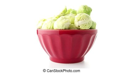 Fresh brussels sprouts on red ceramic bowl isolated on white...