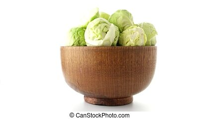 Fresh brussels sprouts on brown wood bowl isolated on white...