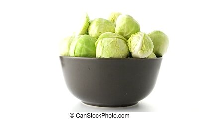 Fresh brussels sprouts on brown ceramic bowl isolated on...