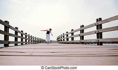 Balance beam - Girl walks away from camera balancing on the...