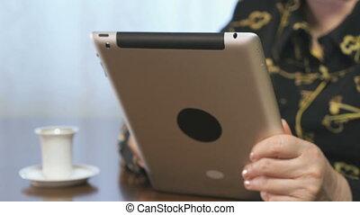 Female hands flipping through a digital food magazine using a digital tablet