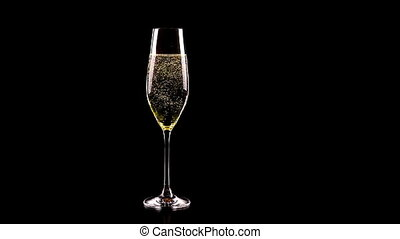flute of champagne with golden bubbles against black...
