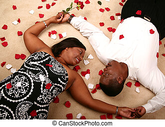 African American Couple Laying On The Floor With Rose Petal...