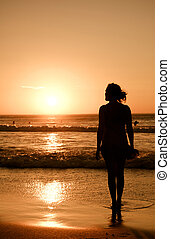 wet feet - A pretty girl stands at the oceans edge looking...
