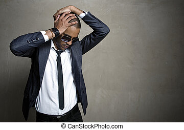 Fashion pose - Male model poses in his sharp suit in front...