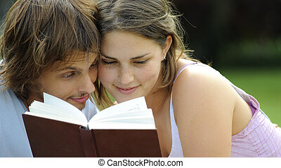 Candid reading - Attractive couple read together in the park