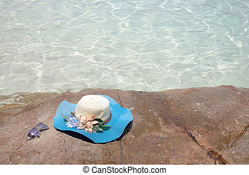 beautiful blue hat and sunglasses on the stone with see view...