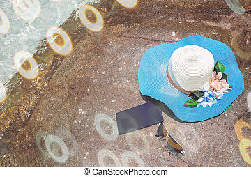 beautiful blue hat , mobile and sunglasses on the stone with...