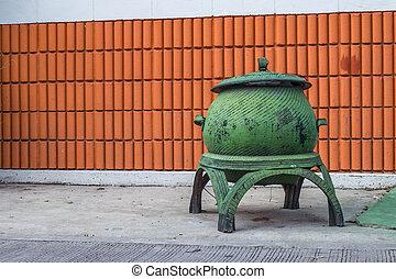 trash bin in front of a brick wall