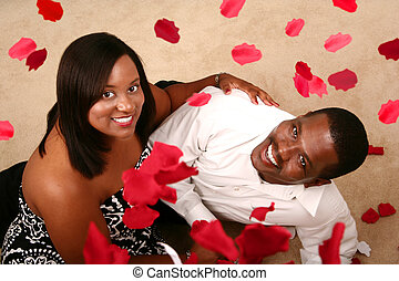 Romantic African American Couple Watching Falling Rose Petal...