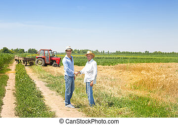 Agribusiness deal - Farmer and businessman shaking hands on...