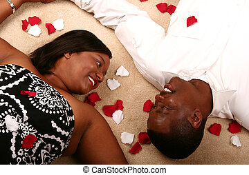 African American Couple Laying On The Floor With Rose Petal