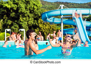 Young couple in swimming pool on sunny day. Water slide. -...