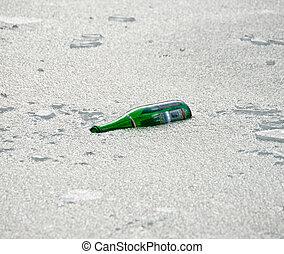 Empty bottle in lake ice
