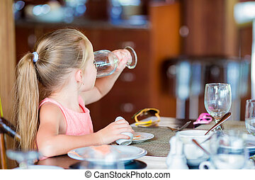 Little girl have breakfast drinking water at outdoor cafe -...