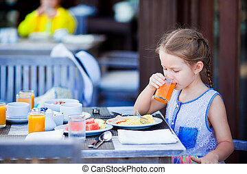 Adorable little girl have breakfast drinking juice at...