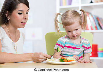 Child girl looks with disgust at healthy vegetables. Mother...