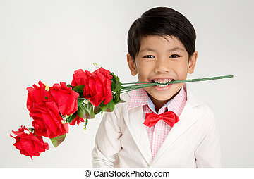 Little Asian boy in vintage suit with red rose Over gray...