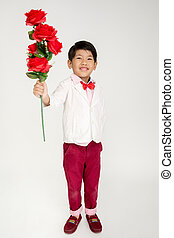 Little Asian boy in vintage suit with red rose in hand Over...