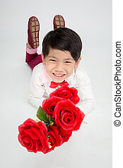 Little Asian boy in vintage suit with red rose in hand. Over...