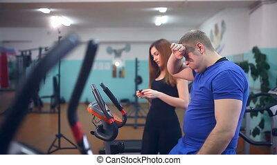 man male athlete drinking water in the gym trainers