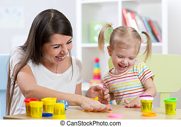 Young pretty woman and child girl playing with colorful clay...