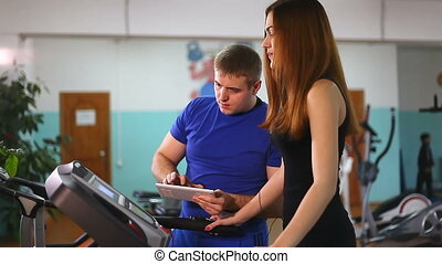 woman runs on a treadmill, man with tablet manager, a gym...