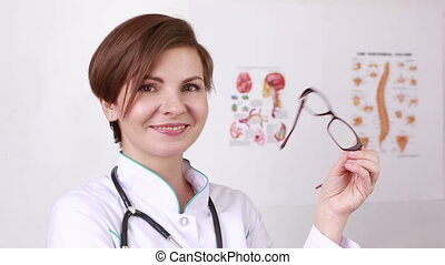 woman doctor with a stethoscope takes off his glasses...