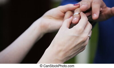 Bride putting a ring on groom