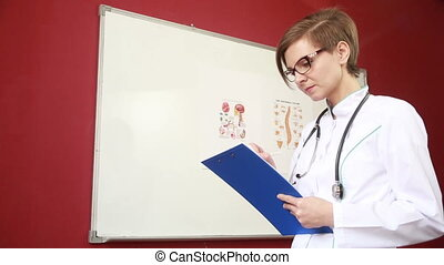 doctor fills the paper. girl in a white coat with a stethoscope writes on the tablet
