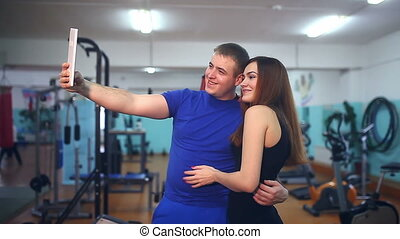 man and woman in a gym doing self on the tablet athletes...