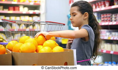 girl with tablet in supermarket to buy orange - girl with...