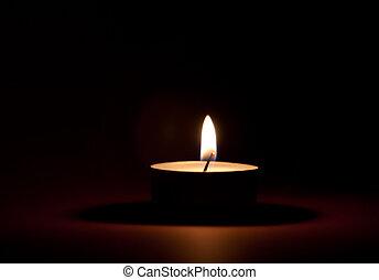 Tea Light - Burning tea light on black background