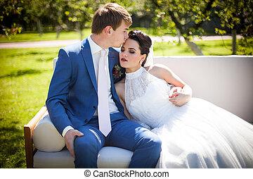 Happy, romantic couple of newlyweds posing & kissing on white sofa