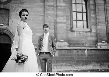 Beautiful brunette bride posing with bouquet, church & groom background b&w