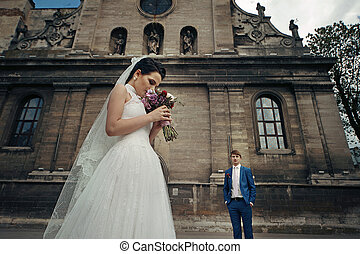Beautiful brunette bride posing with bouquet, church & groom background