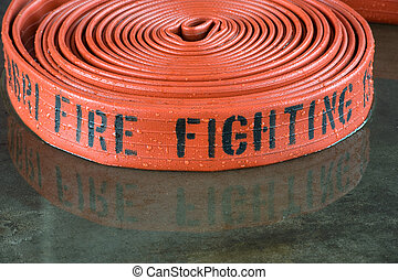 Firehose - A rolled up firehose on the wet floor in a...