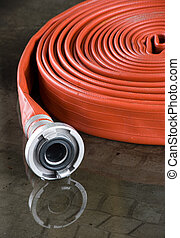 Firehose - A rolled up firehose on the floor in a...