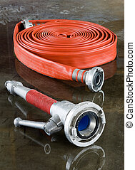 Firehose and nozzle - A rolled up firehose and a nozzle on...