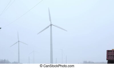 windmills near the road foggy morning. near cars are passing