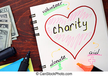 Charity written on notepad on a table.