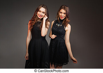 Two cheerful women in black dresses going to party together...