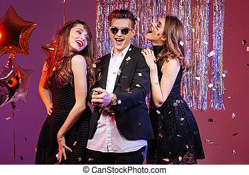 Joyful man dancing and having fun with two seductive women