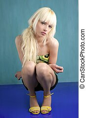 blonde fashion teen young girl squatting green background