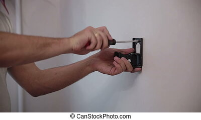 Man installs the holder bracket on the wall - Man installs...